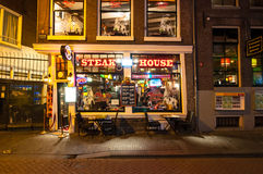 Row of local steakhouses and restaurants at night in red-light district in Amsterdam, the Netherlands. Royalty Free Stock Image