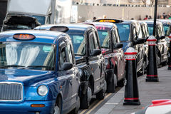 Row Of London Black Taxi Cabs Waiting For Fares. A row of several London black taxi cabs parked waiting for fares royalty free stock image