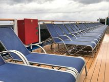 Lounge chairs lined up a cruise ship deck. A row of Lounge chairs lined up a cruise ship deck royalty free stock photo