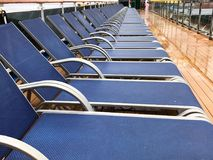 Lounge chairs lined up a cruise ship deck. A row of Lounge chairs lined up a cruise ship deck royalty free stock photography