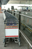 Row of luggage carts with blank billboard Royalty Free Stock Image