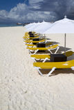 Row of Lunge Chairs and Umbrellas. Rows of several lounge chairs and umbrellas on the beach Stock Images