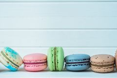 Row of macaroons or macaron on a white wooden background close-up, almond cookies on a table, copy space. Row of macaroons or macaron on a white wooden Stock Image
