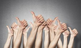 Row of man hands showing thumb up gesture. Agreement and approval group of signs. Human hands gesturing on background of grey wall. Many arms raised together royalty free illustration