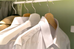 Row of the man white shirt on the hanger. Row of the male white shirt on the hanger Royalty Free Stock Images