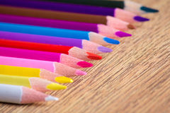 Row of many colorful drawing pencils on wooden table Royalty Free Stock Photo