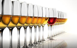 Row of many white wine glasses, with a red one. Stock Images