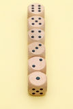 Row of many wooden dice. On a yellow background Royalty Free Stock Image