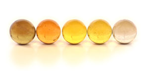 Row of Marbles. A row of yellow glass marbles on white Royalty Free Stock Photography