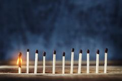 Row of matches, one match burns and fades. Row of matches, one is lit. One burning match to the left of the rest. Concept of the idea. Top place for text Stock Photo
