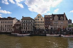 Row of medieval buildings along Lys River dutch: Leie with tourist boats near the bank. stock photography