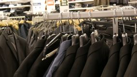 A row of men`s jackets on a hanger at a men`s clothing store in mall. Various men`s suits hanging in the shopping center. A row of men`s jackets on a hanger at a stock video
