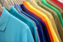 Row of men`s polo shirts in wardrobe or store Stock Images