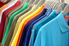 Row of men`s polo shirts in wardrobe or store Royalty Free Stock Image