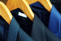 Row of men`s suits hanging in closet.  stock image