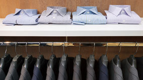 Row of men suit jackets on hangers and shelf with shirt Stock Image