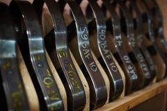Metallic workpieces. Row of metallic workpieces for shoe soles on wooden shelf in cobbler workshop Royalty Free Stock Photography