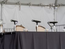 Row of microphones sitting on table, awaiting speakers royalty free stock photography