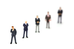 Row of miniature business men. A group of miniature businessmen standing in a row diagonally. Focus in on the man in the bottom left corner. The rest of out of Royalty Free Stock Photos