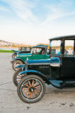 Row of Model T Cars. A row of classic Ford Model T automobiles parked in a lot. Blue sky with wispy white clouds. Vertical.  Copy space Stock Images