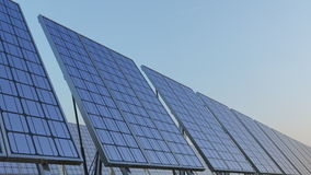 Row of modern solar panels against blue sky. Renewable solar energy generation. 4K seamless loopable clip. ProRes stock video footage