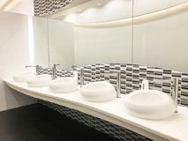 Row of modern white ceramic wash basin in public restroom or res. Row of modern white ceramic wash basin in public toilet or restaurant or hotel or shopping mall Royalty Free Stock Photos