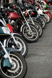 Row of motobikes. Row of motocycles parked on a street in front a motorcycle store Stock Image