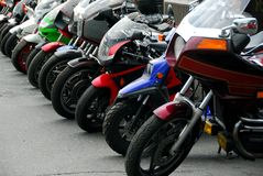 Row of motocycles. Parked on a street in front a motorcycle store Stock Photos