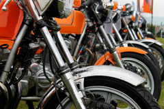 Row of motorbikes. In a field Royalty Free Stock Image