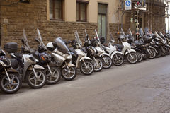 Row of motorbikes. Florence, Italy - 4 September, 2016: A row of parked motorbikes on the street. Compact kinds of transport are very popular in Florence due to Stock Photo