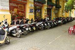 Line of motorbikes. A row of motorbikes parked here by their owners while they work in  Ho Chi Minh City, Vietnam Stock Images