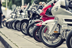 Row of motorcycles parked on a street Royalty Free Stock Images