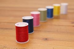 Row of multi-colored cotton reels or bobbins on a wooden sewing. Table Royalty Free Stock Photo
