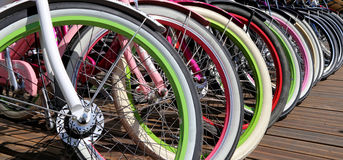 Row multicolored bicycle wheels closeup Stock Image