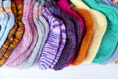 Row of multicolored hand-knitted baby socks Royalty Free Stock Photos