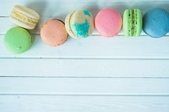 A row of multicolored macaroons or macaron on a white wooden background close-up, almond cookies on a table. Top view. A row of multicolored pasta or macaroni on Royalty Free Stock Photo
