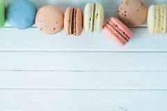 Row of multicolored macaroons or macaron on a white wooden background close-up, almond cookies on a table, copy space. Row of multicolored pasta or macaroni on Stock Image