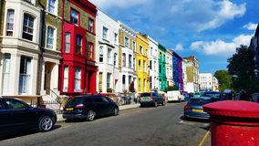Row of multicoloured houses in London. Several multicoloured terraced houses on a street near Portobello road, London. Taken during the summer with bright blue Royalty Free Stock Photography