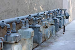 Row of natural gas meters. A row of natural gas meters is attached to a stucco building Royalty Free Stock Image