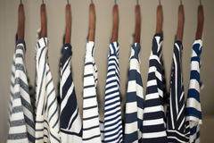 A row of navy striped tops for women on wooden hangers in a closet royalty free stock images