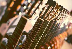 Row of new acoustic guitars in music shop. Close up tuning pegs of new acoustic guitars in music shop Stock Photo