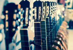 Row of new acoustic guitars in music shop. Close up of tuning pegs new acoustic guitars in music shop Royalty Free Stock Photo