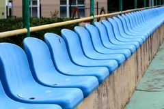 Row of new blue plastic seats mounted on top of concrete bleachers with metal fence and garden vegetation in background next to. Basketball court on warm sunny royalty free stock images