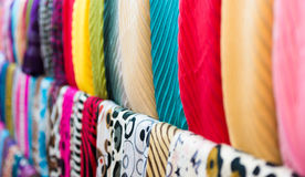 Row of new multicolored scarves at shop. Royalty Free Stock Photography