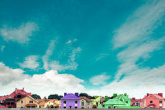 Row of new multicolored townhouses on the background of blue sky. Stock Photos