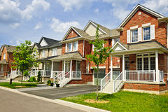 Row of new suburban homes. Suburban residential street with row of red brick houses Stock Photo