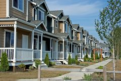 Row of Newer Townhouses. This is a newer neighborhood with a row of beautiful townhouses against a bright blue sky Stock Image