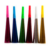 Row of noise makers on white. A row of noise makers including red, blue, green, pink, silver and goal on a white background royalty free stock images