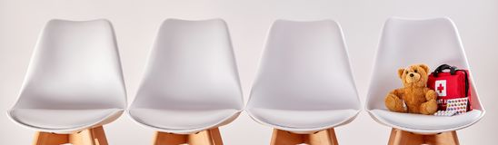 Free Row Of Chairs With Teddy Bear And First Aid Kit Stock Images - 107969184
