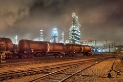 Free Row Of Train Wagons With An Illuminated Oil Refinery At Night In Port Of Antwerp, Belgium Royalty Free Stock Photo - 134491135